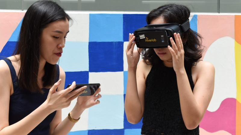 This photo taken on March 10, 2020 shows Seow Yun Rong (L) guiding student Elizabeth Lee through a virtual reality simulation designed to help students respond to sexual harassment at the Nanyang Technological University in Singapore. - The VR technology is part of the Girl, Talk project which is aimed at helping women fight back against harassment in Singapore. (Photo | AFP)