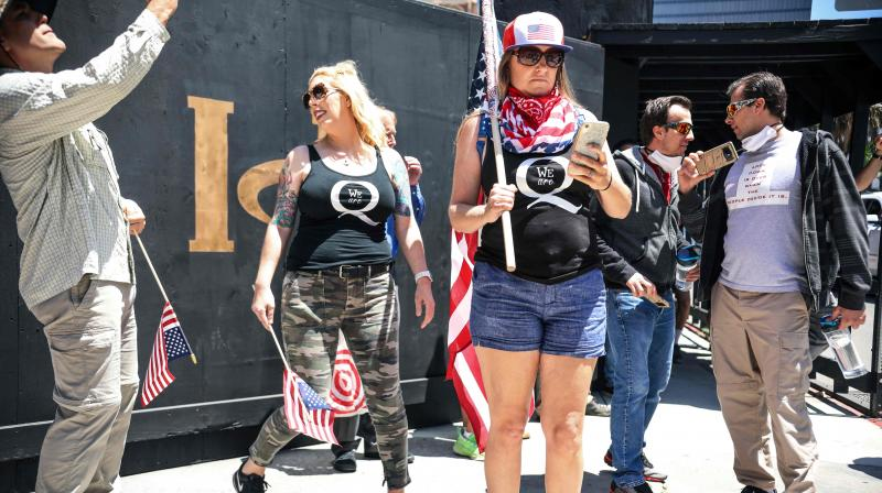 Conspiracy theorist QAnon demonstrators protest during a rally to re-open California and against Stay-At-Home directives on May 1, 2020 in San Diego, California. (Photo | AFP)