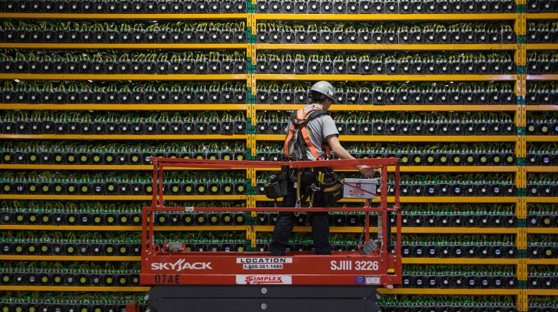 In this file photo taken on March 19, 2018 a technician inspects bitcoin mining at Bitfarms in Saint Hyacinthe, Quebec. (Photo | AFP)