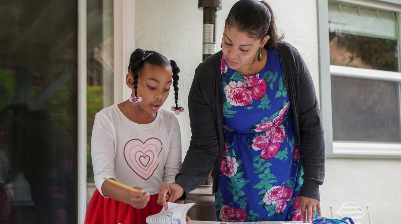 Adrienne Williams does school work with her daughter Gia, 7, at her mother's house in Pinole, California, on May 13, 2020. - She delivers for Amazon, but Adrienne Williams says the e-commerce and tech giant did not deliver for her. The 42-year-old California single mother is among the legion of drivers for Amazon's third-party delivery firms which have been struggling amid surging demand for goods and supplies to locked-down consumers during the pandemic. (Photo | AFP)