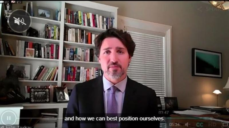"""A screenshot of Prime Minister Justin Trudeau at a Parliament session being held over Zoom. Trudeau went for the typical bookcase background, while another MP streamed in front of a white bedsheet meant to hide home renovations, which was described as looking like a """"hostage video situation"""", and Industry Minister Navdeep Bains, a devout Sikh, won praise from viewers for using a painting of colorful turbans as a backdrop."""