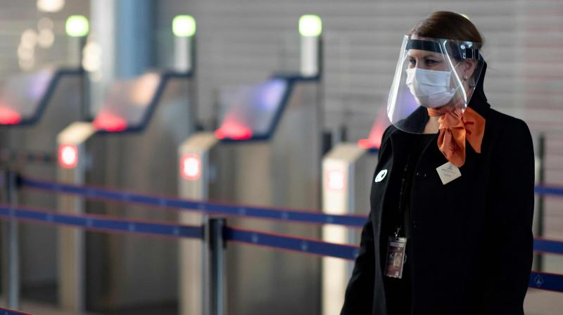 In this file photo taken on May 14, 2020 a member of Charles de Gaulle airport personnel wears a protective face mask and visor in Terminal 2 of Charles de Gaulle international airport in Roissy near Paris, as France eases lockdown measures taken to curb the spread of the COVID-19 (the novel coronavirus). (Photo | AFP)