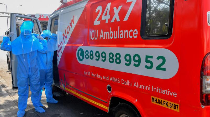 In this photograph taken on May 24, 2020, ambulance staff from HelpNow put on protective gear before starting a transport journey in Mumbai. As coronavirus hotspot Mumbai grapples with crippling healthcare shortages, an ambulance service founded by three students is trying to fill the gap in India's worst-hit city. But many patients are too poor to pay for the life-saving trip. (Photo | AFP)