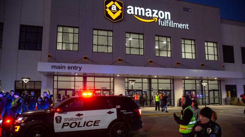 In this file photo taken on December 14, 2018, police officers put barricades during a protest at the Amazon fulfillment center in Shakopee, Minnesota. - Amazon on June 10, 2020, announced a one-year ban on letting police use its facial recognition technology, calling for strong government regulations for its ethical use. The moratorium comes after repeated calls by critics and racial justice groups for Amazon's cloud computing unit to stop providing police and immigration officials with tools that can be used to unfairly target people based on race. (Photo   AFP)