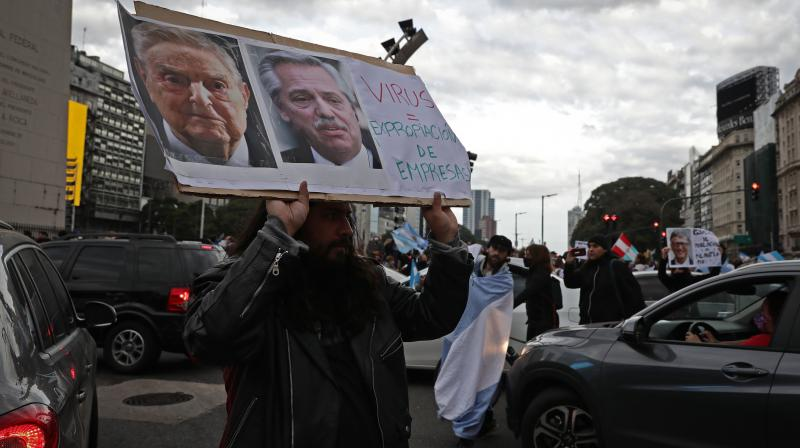 Not just for the Black Lives Matter protests, George Soros is also being blamed by conspiracy theorists for the pandemic. In this image, a man holds a sign with the images of Hungarian-US billionaire George Soros (L) and Argentina's President Alberto Fernandez, reading
