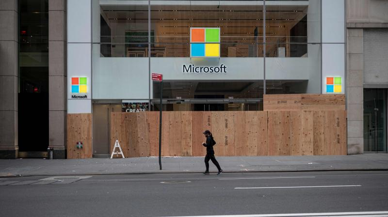 "In this file photo taken on June 2, 2020 A looted and boarded up Microsoft store is seen after a night of protest over the death of an African-American man George Floyd in Minneapolis in Manhattan in New York City. Microsoft's physical stores, which sold Surface tablets, laptops and XBox gaming gear, never gained the momentum of rival Apple. Its retail team members will ""serve customers from Microsoft corporate facilities and remotely provide sales, training, and support,"" the company said. (Photo 