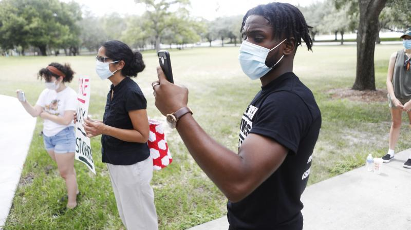 Black workers account for 3.8% of all U.S. Facebook employees and 1.5% of all U.S. technical workers at the company. Those numbers have barely budged over the past several years, a common pattern across large Silicon Valley firms. In this picture, Zachary Greene wears a face mask while protesting in front of the Lifsey residence where the USF President Steven Currall lives on campus on July 2, 2020 in Tampa, Florida. Tampa Bay Students for Democratic Society protest at the University of South Florida demanding an increase in Black student enrollment, employ more Black faculty and staff, more financial aid, and make direct connections with the surrounding community. (Photo | AFP)
