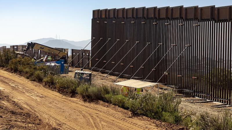 In this June 19, 2019 photo construction crews work on the replacement border wall on the boundary between the United States and Mexico near the Calexico Port of Entry. Customs and Border Protection (CBP), which built the steel wall, plans to install 200 autonomous surveillance towers by 2022, after a two-year pilot project using four. (Photo | Wikimedia Commons - Mani Albrecht of U.S. Customs and Border Protection Office of Public Affairs)