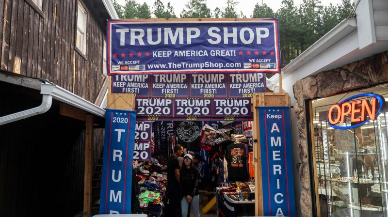 "Tourists browse a gift store featuring US President Donald Trump campaign items in Keystone, South Dakota on July 2, 2020. Social media is virtually a Trump shop full of buyers. On Twitter, Donald Trump's 82.4 million followers dwarf Joe Biden's 6.4 million. The president has spent years cultivating a ragtag digital ""army"" of meme makers and political influencers who retweet campaign messages hundreds of times daily. Trump is outspending Biden on Google and YouTube advertising by nearly 3 to 1. (Photo 