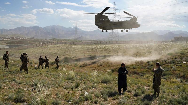 In this file photo taken on June 6, 2019 a US military Chinook helicopter lands on a field outside the governor's palace during a visit by the commander of US and NATO forces in Afghanistan, General Scott Miller, and Asadullah Khalid, acting minister of defense of Afghanistan, in Maidan Shar, capital of Wardak province. US President Donald Trump denied on June 28, 2020 being briefed on intelligence that reportedly showed Russia had offered bounties to Taliban-linked militants for killing US soldiers in Afghanistan. (Photo | AFP)