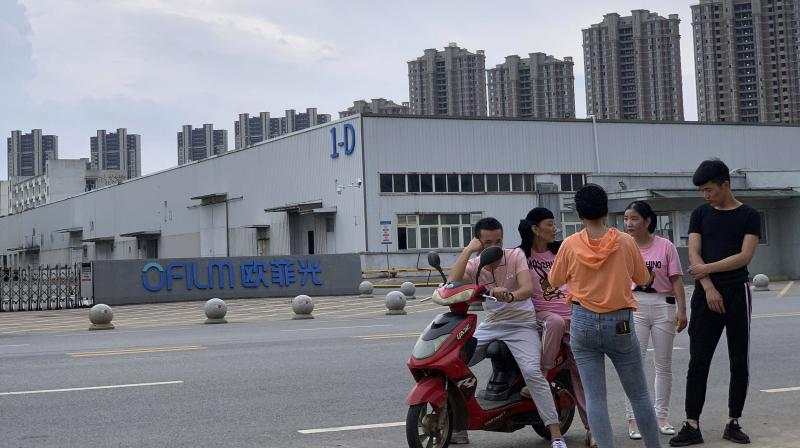 """n this June 5, 2019, file photo, neighborhood residents chat near the entrance to an OFILM factory in Nanchang in eastern China's Jiangxi province. The company is one of 11 that the U.S. government has imposed trade sanctions on and says are implicated in human rights abuses in Xinjiang. """"This action will ensure that our goods and technologies are not used in the Chinese Communist Party's despicable offensive against defenceless Muslim minority populations,"""" said Commerce Secretary Wilbur Ross in a statement. (Photo 