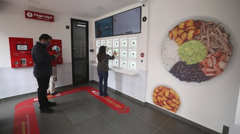A woman picks up her order from a locker at a MUY restaurant, a Colombian fast food chain that is planning to turn its branches into automated restaurants, in Bogota, Colombia, Thursday, Aug. 13, 2020. The chain has opened its first 'contactless store' in a commercial district of Bogota, where many restaurants have been forced to shut down because of a ban on sit-down dining. (Photo | AP)