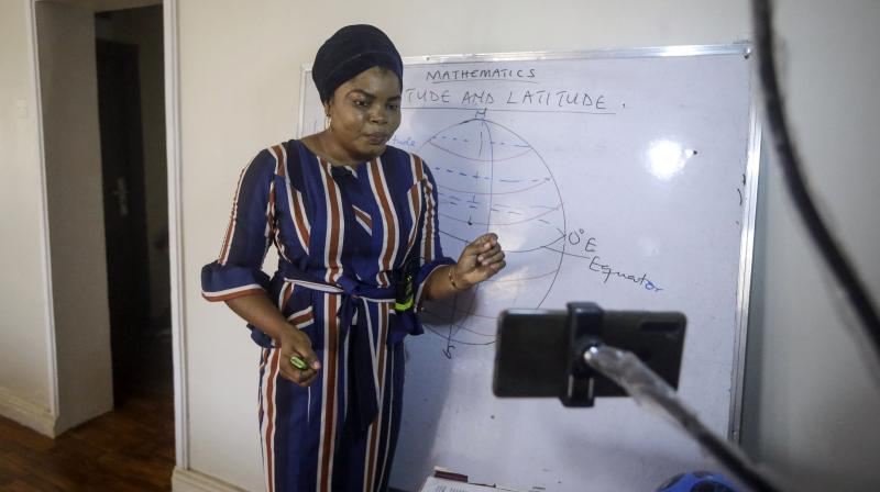 Mathematics teacher Basirat Olamide Ajayi, 36, teaches probability theory with the aid of playing cards, online via her mobile phone from her house in Lagos, Nigeria Saturday, Aug. 15, 2020. Ajayi's free classes are attracting students from all over Nigeria, and now students abroad are joining. A recent request came from Canada. Ajayi says she is beginning to see herself as a global teacher. (Photo | AP)