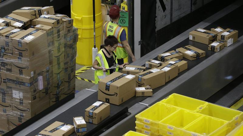 Amazon customers can now read detailed product information, manage account settings, track orders, view account history, pay bills, and recharge their phone or DTH services in Tamil, Kannada, Telugu and Malayalam in addition to English and Hindi. This photo shows Amazon workers checking packages moving down a conveyor system that leads to a shipping area at an Amazon 'fulfilment' centre. (Photo | AP)