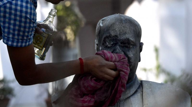 A police official along with a group of people clean the bust of Dr Syama Prasad Mukherjee after it was vandalised at Keoratola Mohasoshan in Kolkata. (Photo: Abhijit Mykherjee)