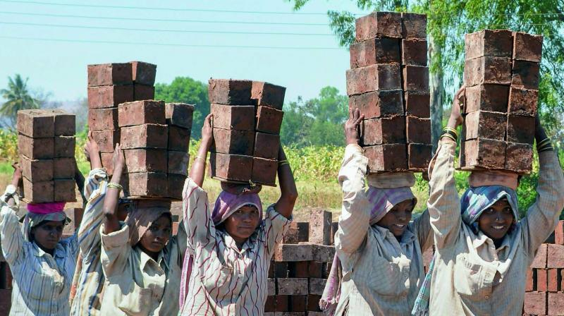 A group of brick factory workers carry bricks on their heads ahead of International Women's Day in Karad, Maharashtra. (Photo: PTI)