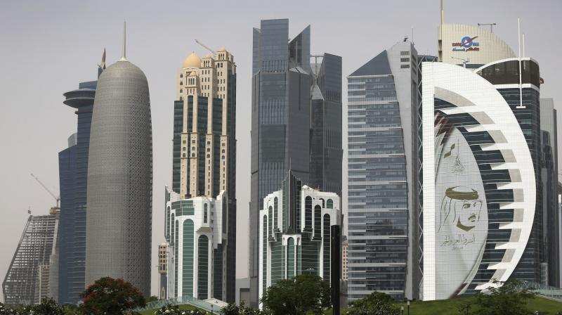 In this May 5, 2018 photo, a giant image of the Emir of Qatar Sheikh Tamim bin Hamad Al Thani, adorns a tower in Doha, Qatar. Saudi Arabia will open its airspace and land border to Qatar in the first step toward ending a years-long diplomatic crisis  that deeply divided US defense partners.  (AP/Kamran Jebreili)