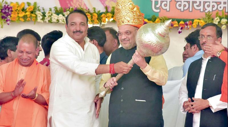 Congress MLC Dinesh Pratap Singh presents a memento to BJP president Amit Shah in the presence of Uttar Pradesh chief minister Yogi Adityanath at a rally in Rae Bareli on Saturday. (Photo: PTI )
