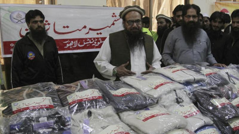 Hafiz Saeed, center, leader of the Jamaat-ud-Dawa looks at relief goods his party workers collected for Pakistani Kashmiris who are displaced due to Indian firing at the Line of Control between Pakistan and Indian Kashmir. (Photo: AP)