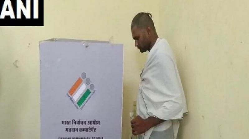 Draped in white attire and with shaven head, the man queued up to vote despite his personal tragedy. (Photo: ANI)
