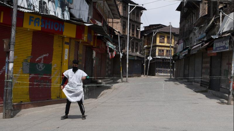 a man stands guard to restrict the entry of outsiders to their locality. Several localities in Srinagar have been declared red zones and severe containment measures have been taken up. (DC Photo: H U Naqash)