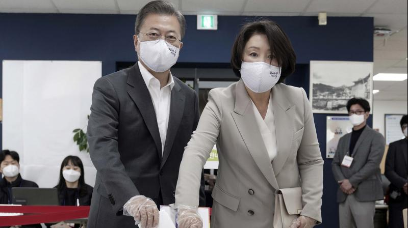 Wearing face masks to help protect against the spread of the new coronavirus, South Korean president Moon Jae-in (left) and his wife Kim Jung-sook pose as they cast their votes in the election at a polling station in Seoul, South Korea on April 10, 2020. (AP)