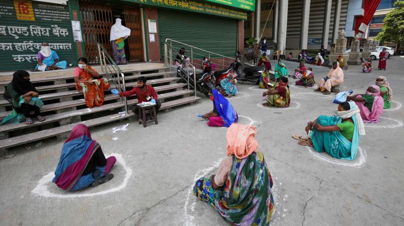 Women sit in social distance circles outside a bank as they wait to collect their pension in Bhopal. (AFP)