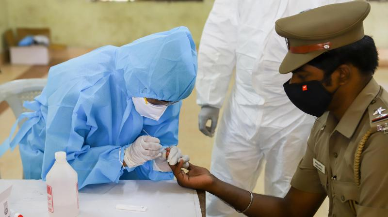 A police officer gives a sample for a coronavirus rapid test in Chennai on Sunday, April 19, 2020. (PTI)