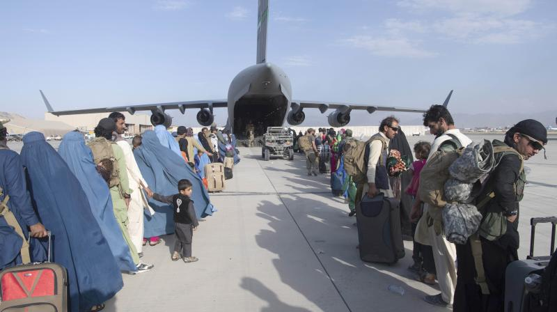 In this image provided by the U.S. Air Force, U.S. Air Force loadmasters and pilots assigned to the 816th Expeditionary Airlift Squadron, load people being evacuated from Afghanistan onto a U.S. Air Force C-17 Globemaster III at Hamid Karzai International Airport in Kabul, Afghanistan. (Photo: AP)