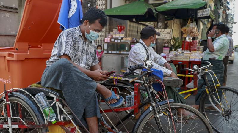 A rickshaw driver checks his mobile phone in Yangon, Myanmar, Tuesday, February 4, 2021. Myanmar's new military government has blocked access to Facebook as resistance to Monday's coup surged amid calls for civil disobedience to protest the ousting of the elected civilian government and its leader Aung San Suu Kyi. (AP)