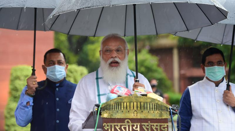 Prime Minister Narendra Modi addresses the media, as it rains on the first day of the Monsoon Session of Parliament, in New Delhi, Monday, July 19, 2021. Union Ministers Prahlad Joshi and Jitendra Singh are also seen. (PTI Photo)