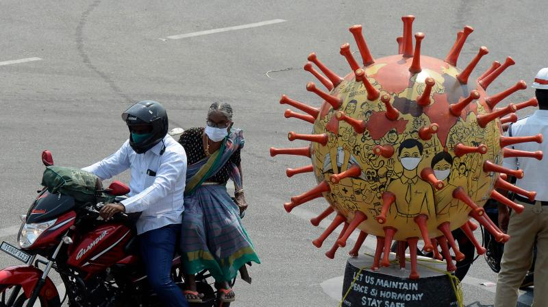 Motorists drive past a coronavirus-themed globe kept at a traffic junction during a government-imposed nationwide lockdown as a preventive measure against the COVID-19 coronavirus, in Hyderabad. PTI Photo