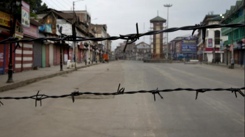 In this August 6, 2019 file photo, a deserted street is seen through a barbwire set up as blockade during curfew in Srinagar. (Photo: AP)