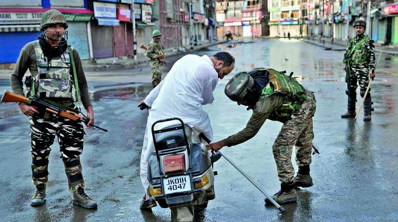 Paramilitary forces check the bag of a man riding a scooter during curfew in Srinagar on Thursday. (Photo: PTI)