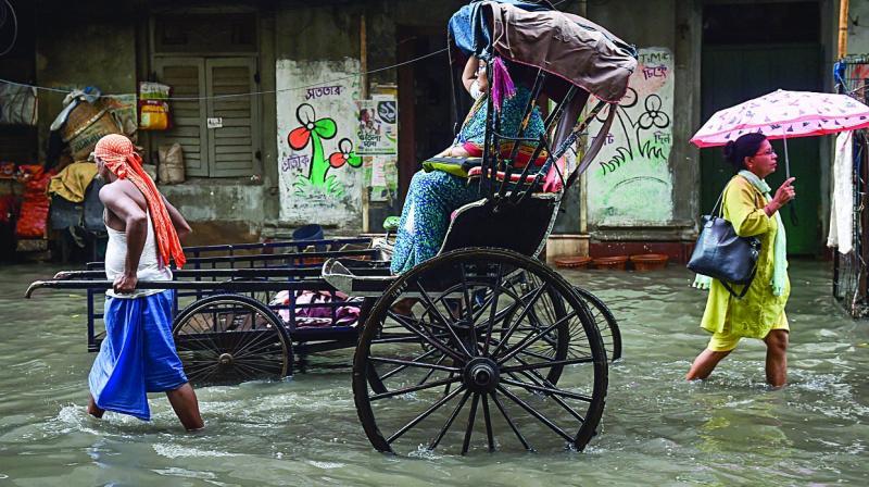 A hand rickshaw puller carries a passenger as another woman passes through a waterlogged street, following monsoon rain in Kolkata on Thursday. (Photo: PTI)