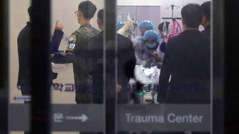 Doctors treat an unidentified person, believed to be a N. Korean soldier who defected, to the South. (Photo: AFP)
