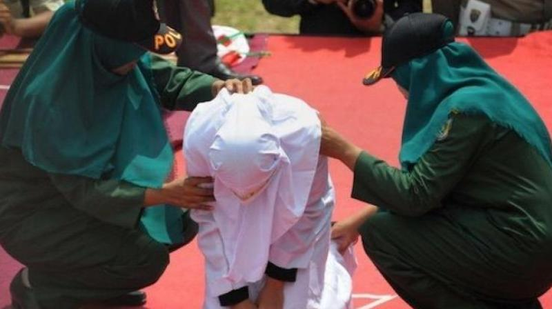The woman was robed in white, had her face covered and then made to kneel on a stage where she was punished in front of a crowd. (Photo: AP)
