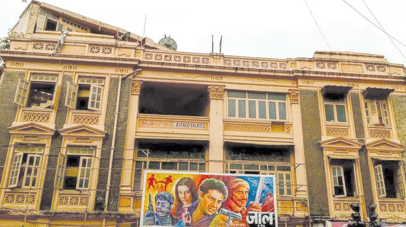 """Alfred Talkies stands apart. Its distinctly European architecture occupies pride of place at a busy intersection, painted in what hopeless artists call """"skin colour"""". (Photo: Mrigank Warrier)"""