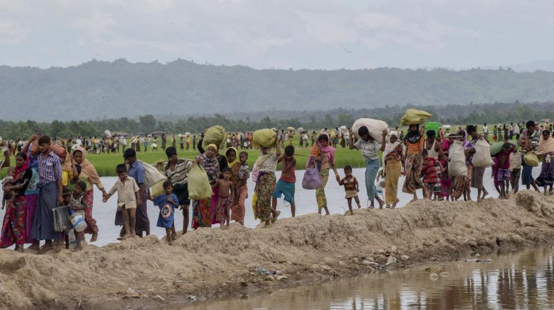 Rohingya Muslims, who spent four days in the open after crossing over from Myanmar into Bangladesh, carry their belongings after they were allowed to proceed towards a refugee camp, at Palong Khali, Bangladesh. (Photo: AP)