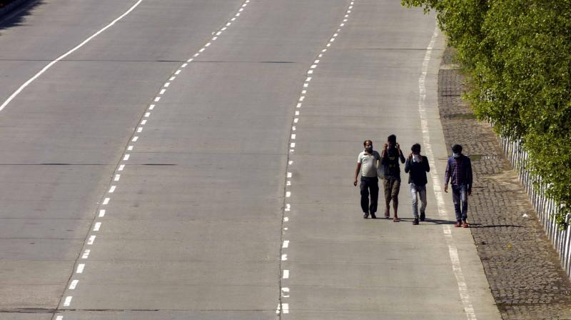 Migrant workers walk down a deserted urban highway to their homes in rural India. (DC Photo: Pritam Bandyopadhyay)