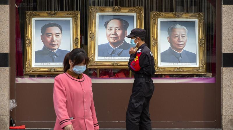 A security guard and worker wearing face masks walk past portraits of Chinese leaders (from left) Zhou Enlai, Mao Zedong, and Liu Shaoqi in the window of a photo studio in Beijing. (AP)