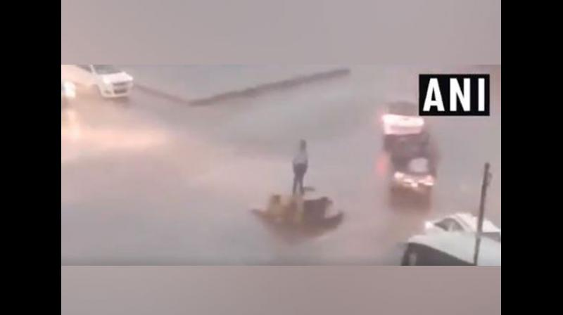 A traffic police constable here became a social media star for his impeccable dedication towards his duty amid a heavy downpour that lashed the state on Sunday. (Photo: ANI)