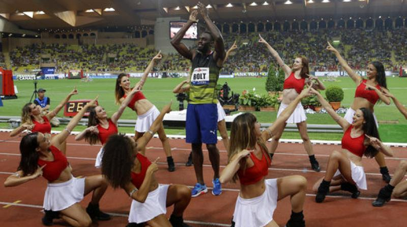 A file photo of Usain Bolt, surrounded by cheerleaders, at the IAAF Diamond League Athletics meeting in Monaco in July. (Photo: AP)