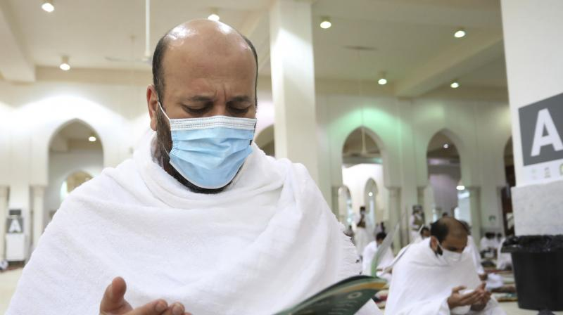 A Muslim pilgrim prays inside the Namira Mosque in Arafat as he wears a mask to protect himself against coronavirus during the annual hajj pilgrimage near the holy city of Mecca, Saudi Arabia. (AP)