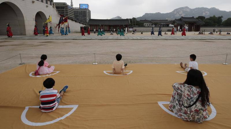 Visitors watch while maintaining social distancing during a re-enactment ceremony of the changing of the Royal Guard at the Gyeongbok Palace, one of South Korea's well-known landmarks, in Seoul, South Korea. (AP)