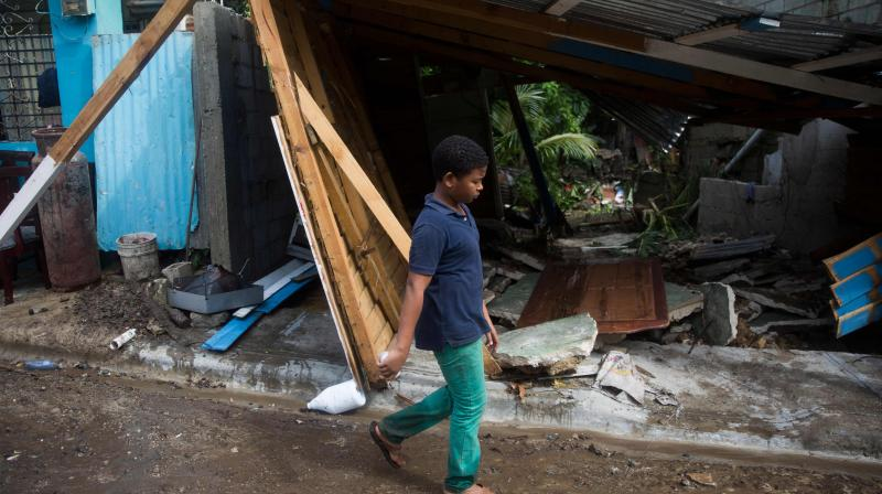 A boy walks past a destroyed house after the overflow of the Magua river due to heavy rains caused by Isaias storm in the city of Hato Mayor, northwest of Santo Domingo, Dominican Republic. (AFP)