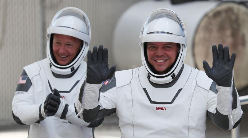 NASA astronauts Bob Behnken (R) and Doug Hurley walk out of the Operations and Checkout Building on their way to the SpaceX Falcon 9 rocket with the Crew Dragon spacecraft on launch pad 39A at the Kennedy Space Center in Cape Canaveral, Florida. (File Image: AFP)
