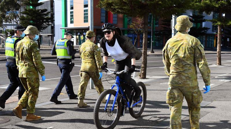 A cyclist passes a group of police and soldiers patrolling the Docklands area of Melbourne. (AFP)