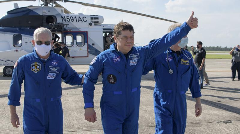 NASA astronaut Robert Behnken gives a thumbs up to onlookers as he boards a plane at Naval Air Station Pensacola to return him and NASA astronaut Douglas Hurley home to Houston a few hours after the duo landed in their SpaceX Crew Dragon Endeavour spacecraft off the coast of Pensacola. (NASA via AP)