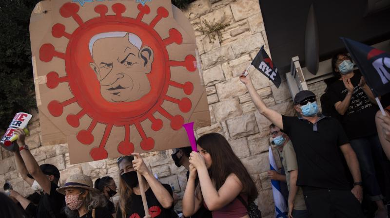 A protester holds a sign depicting Prime Minister Benjamin Netanyahu during a protest a against him outside Prime Minister residence in Jerusalem. (AP)